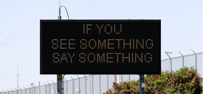 A sign urges citizens to report suspicious activity
